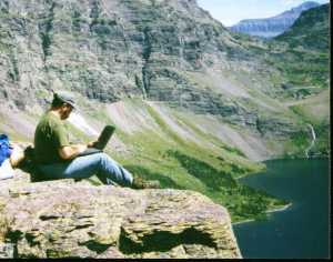 Photo of Bill Binder sitting on a cliff,, typing on a laptop
